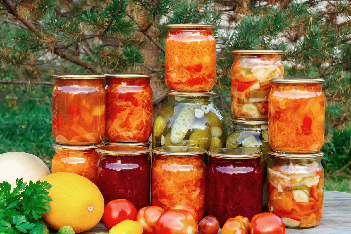 several-homemade-jars-of-canned-vegetables-and-fresh-vegetables-on-a-wooden-table-image