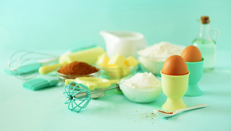 time-to-bake-baking-ingredients-butter-sugar-flour-eggs-oil-spoon-rolling-pin-brush-whisk-milk-over-blue-background-bakery-food-frame-cooking-concept-copy-space
