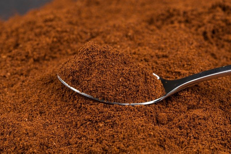 pile-of-ground-coffee-and-a-metal-spoon-close-up