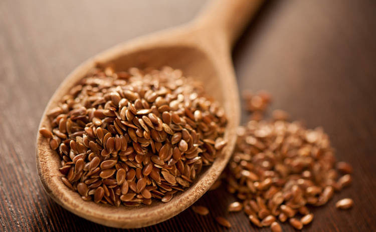 close-up-of-brown-flaxseeds-on-spoon-at-table