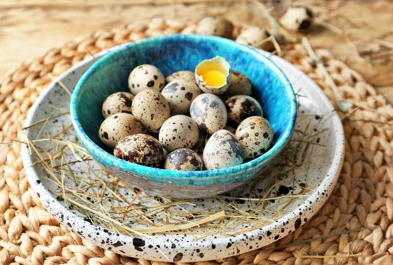 raw-quail-eggs-in-bowl-on-wicker-mat