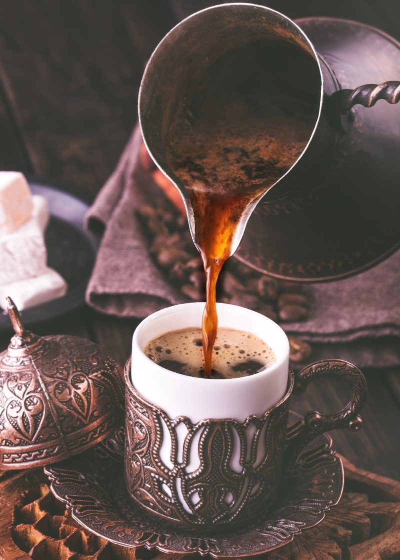 pouring-turkish-coffee-into-traditional-embossed-metal-cup-toned