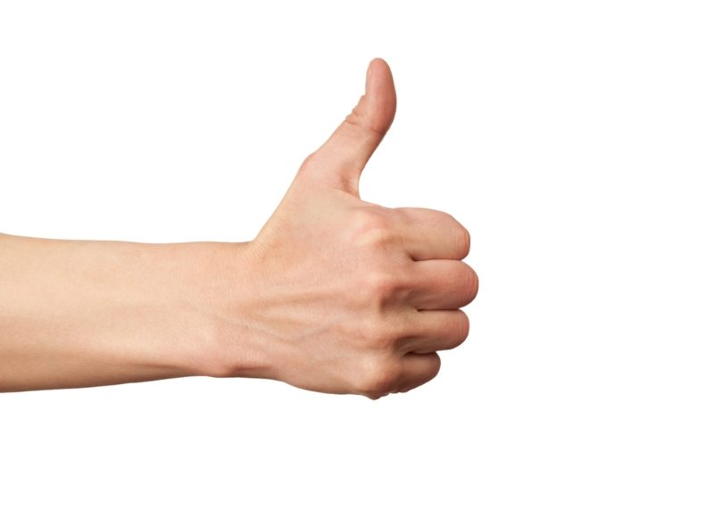 closeup-of-male-hand-showing-thumbs-up-sign-against-white-background